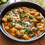 Chickpea spinach curry garnished with coriander leaves served in a black bowl