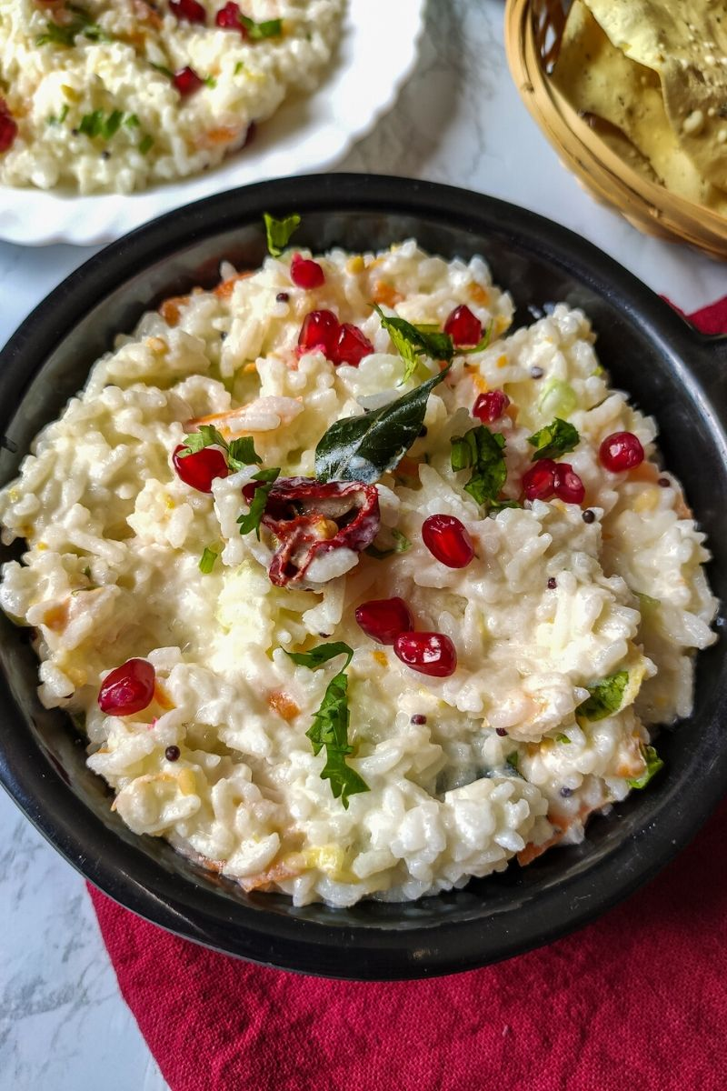 curd rice garnished with pomegranate seeds served in a black bowl kept on a red table napkin