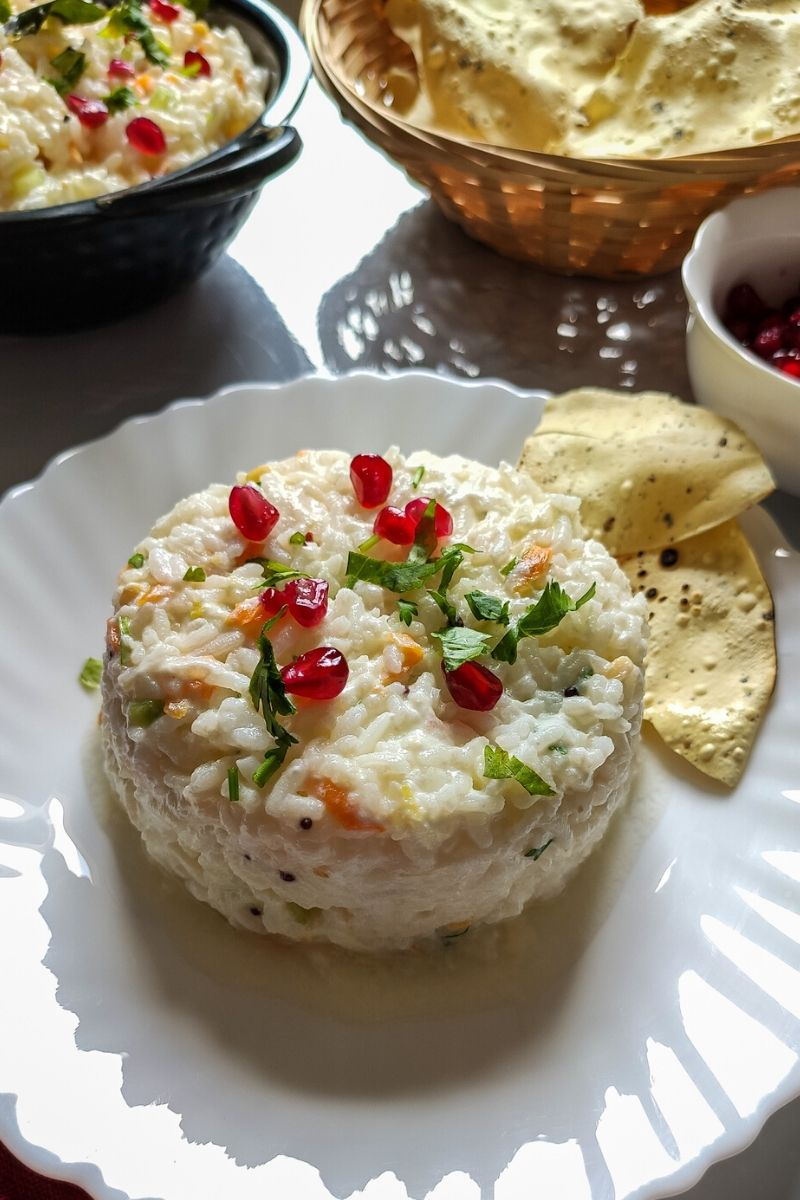 Curd rice garnished with pomegranate seeds served on a white plate with roasted popadums
