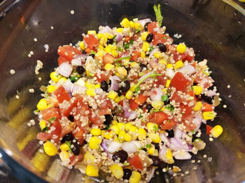 Ingredients of corn and quinoa salad mixed in a large glass bowl