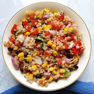 Mexican corn quinoa salad served in a white bowl kept on a blue table napkin