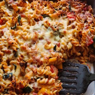 Vegetable baked pasta getting scooped out with a black spatula
