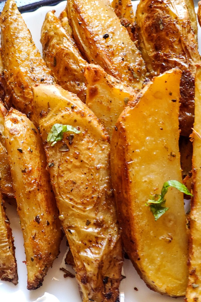 Close up shot of baked potato wedges kept on a white plate and garnished with chopped coriander leaves