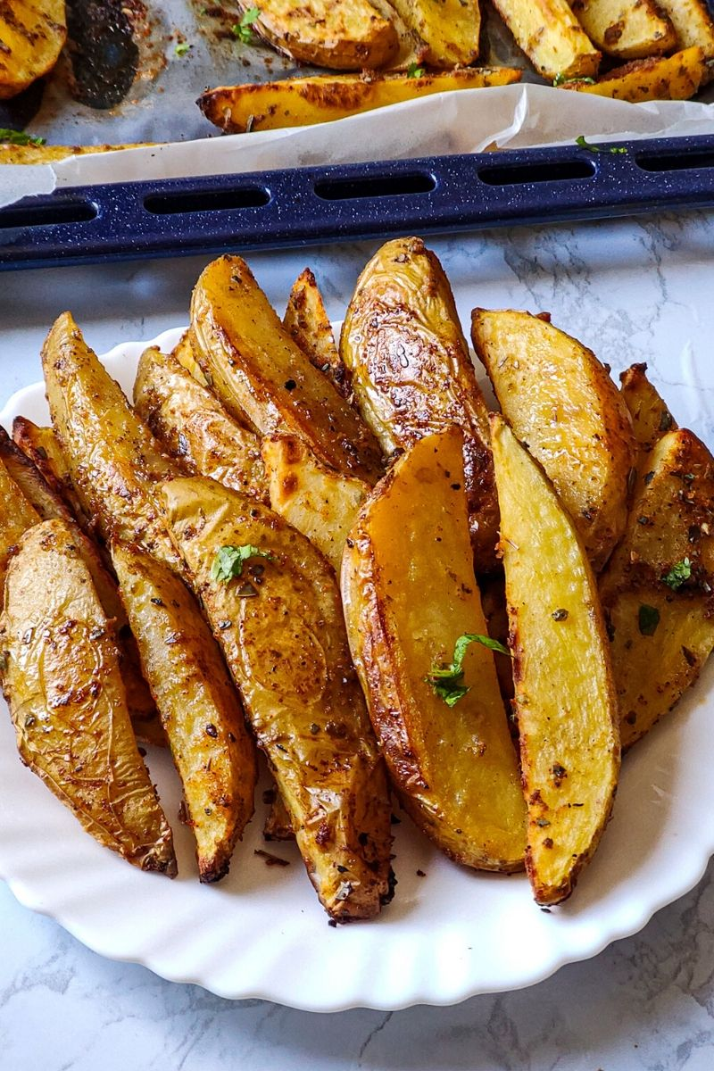 crispy potato wedges served on a white plate and more wedges kept on a baking tray in the background