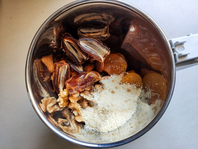 Ingredients of apricot energy balls inside a grinding jar