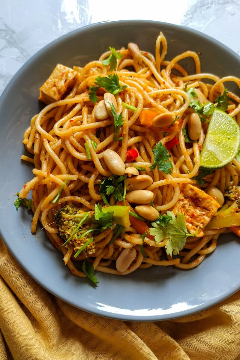 Vegan Thai curry noodles served on a grey plate kept on a yellow table napkin