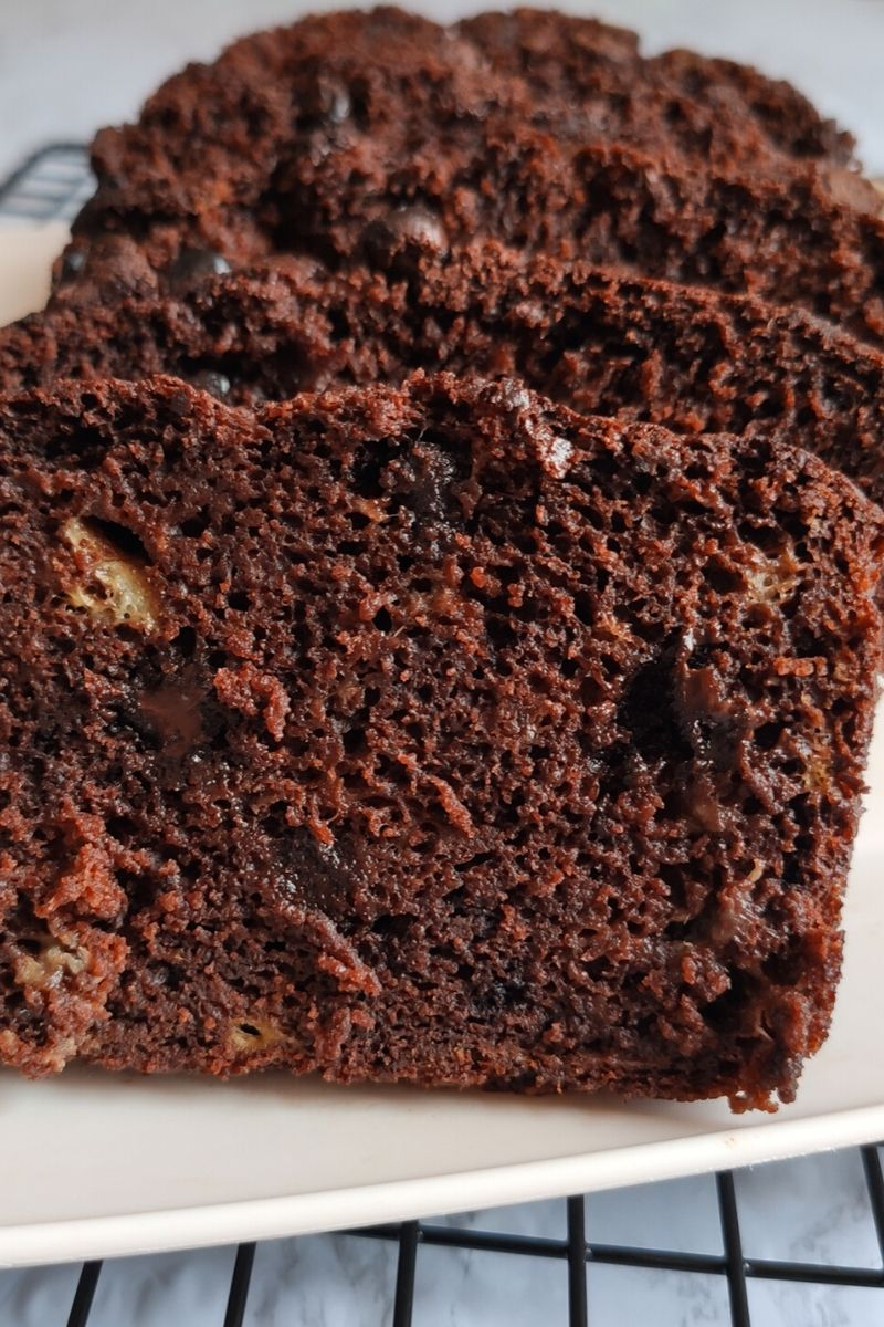 Close up shot of slices of vegan chocolate banana bread served on a white plate