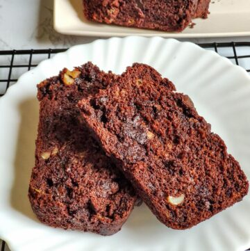 Two slices of vegan chocolate banana bread served on a white plate and another plate of banana bread visible in the background