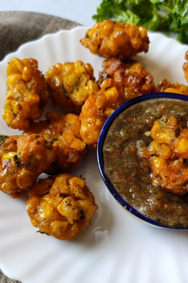one corn fritter dipped in a bowl of chutney and more fritters served on the side