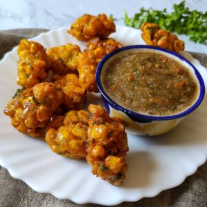Indian corn fritters served on a white plate with chutney in a small bowl on the side and coriander leaves in the background