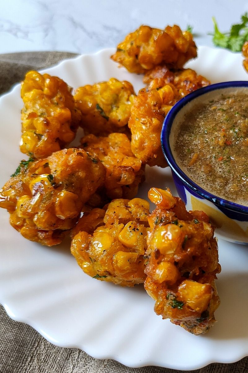 Indian corn fritters served on a white plate with chutney in a small bowl on the side