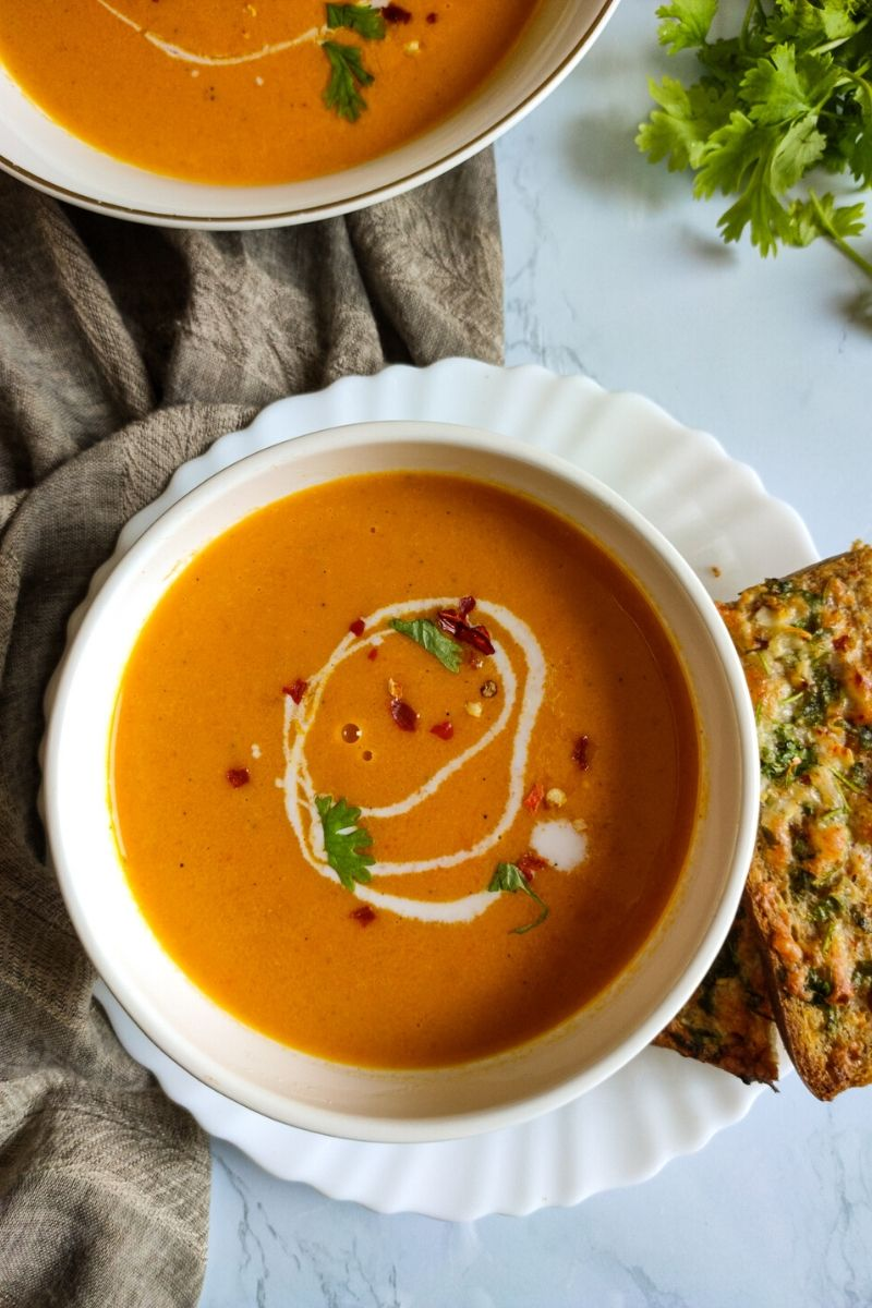 carrot ginger soup garnished with coconut cream, coriander leaves, and chili flakes served in a white bowl with some garlic bread on the side, another bowl of soup in the background
