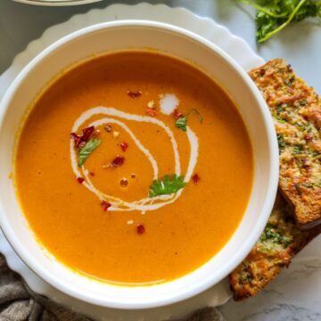carrot ginger soup garnished with coconut cream, coriander leaves, and chili flakes served in a white bowl with some garlic bread on the side