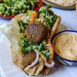Falafel wrap served on a cane basket with a hummus bowl on the side
