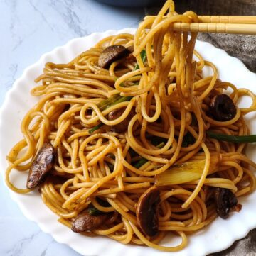 Mushroom noodles getting picked up from a plate with chopsticks