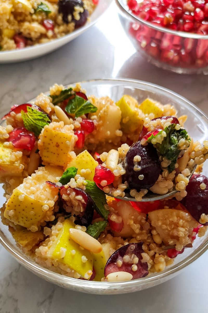 Quinoa fruit salad served on a white plate with pomegranate seeds in the background