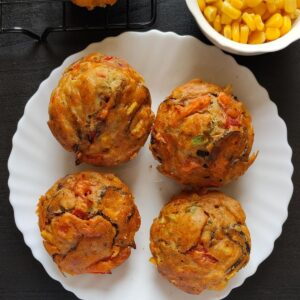 four savoury muffins kept on a whote plate with some corn kernels in the background