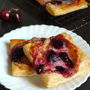 Two cherry cream cheese Danishes on a white plate with some cherries and another danish in the background
