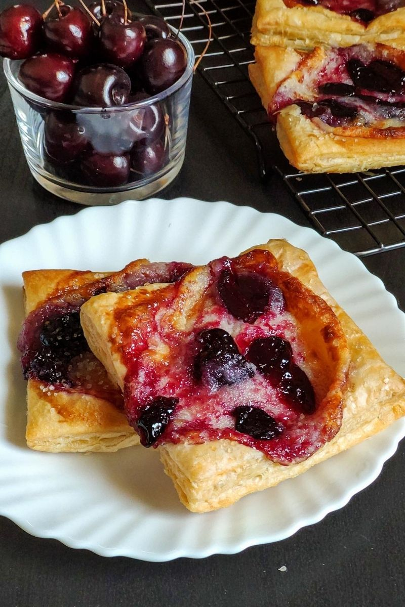Two cherry cheese danishes on a white plate with a bowl of cherries and another danish in the background