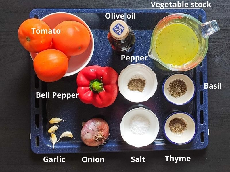 Ingredients for roasted tomato and bell pepper soup on a baking tray