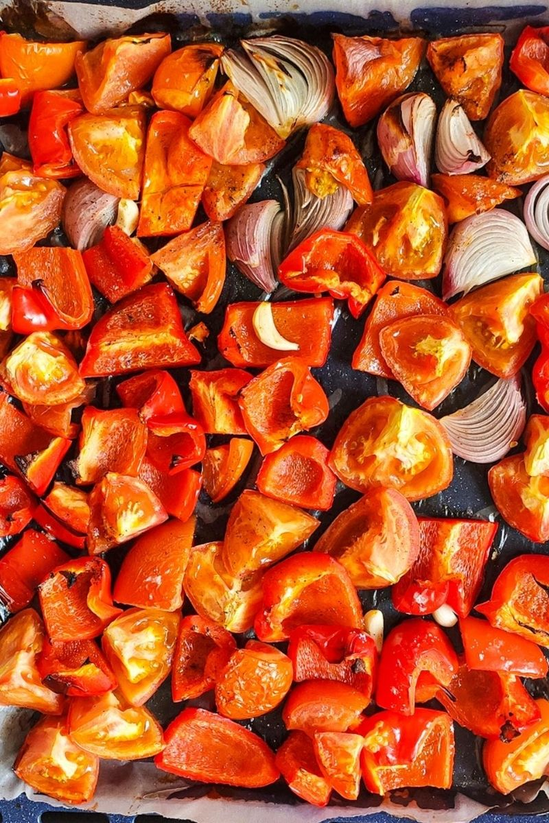 Roasted tomato, red bell pepper, onion, an garlic on a baking tray