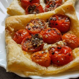 Two tomato puff pastry tarts on a white plate