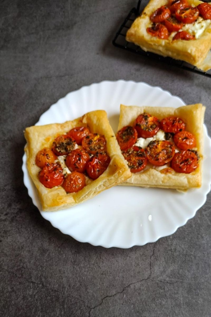 Two tomato puff pastries on a white plate another pastry in the background