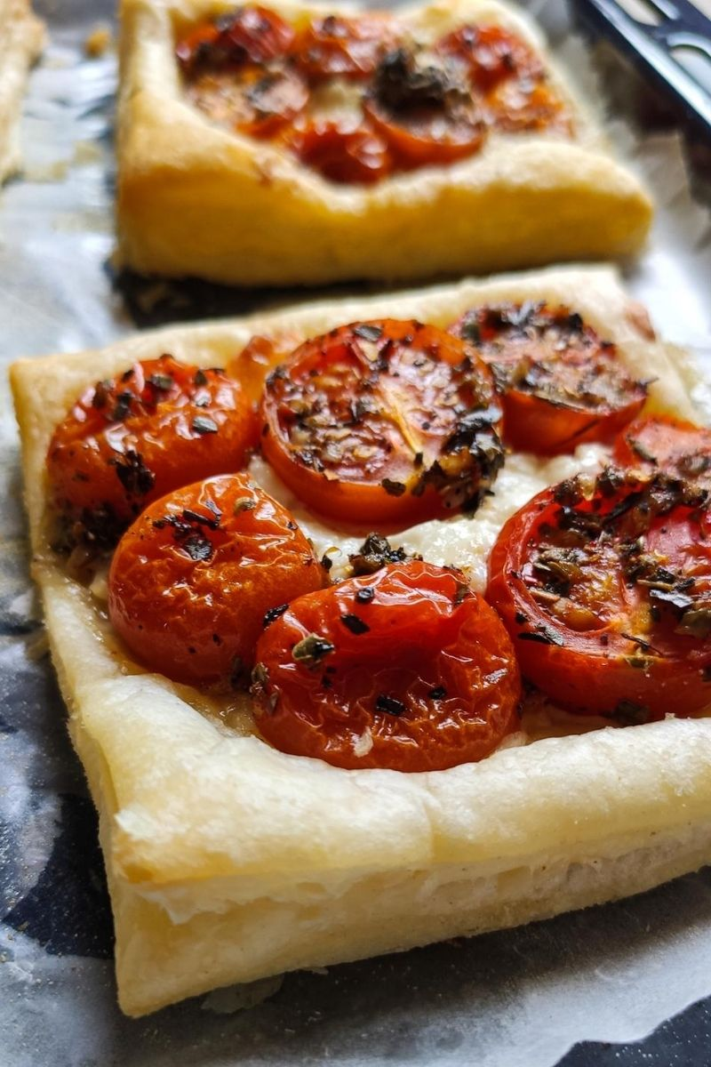 Two tomato cheese puff pastry tarts on a baking tray