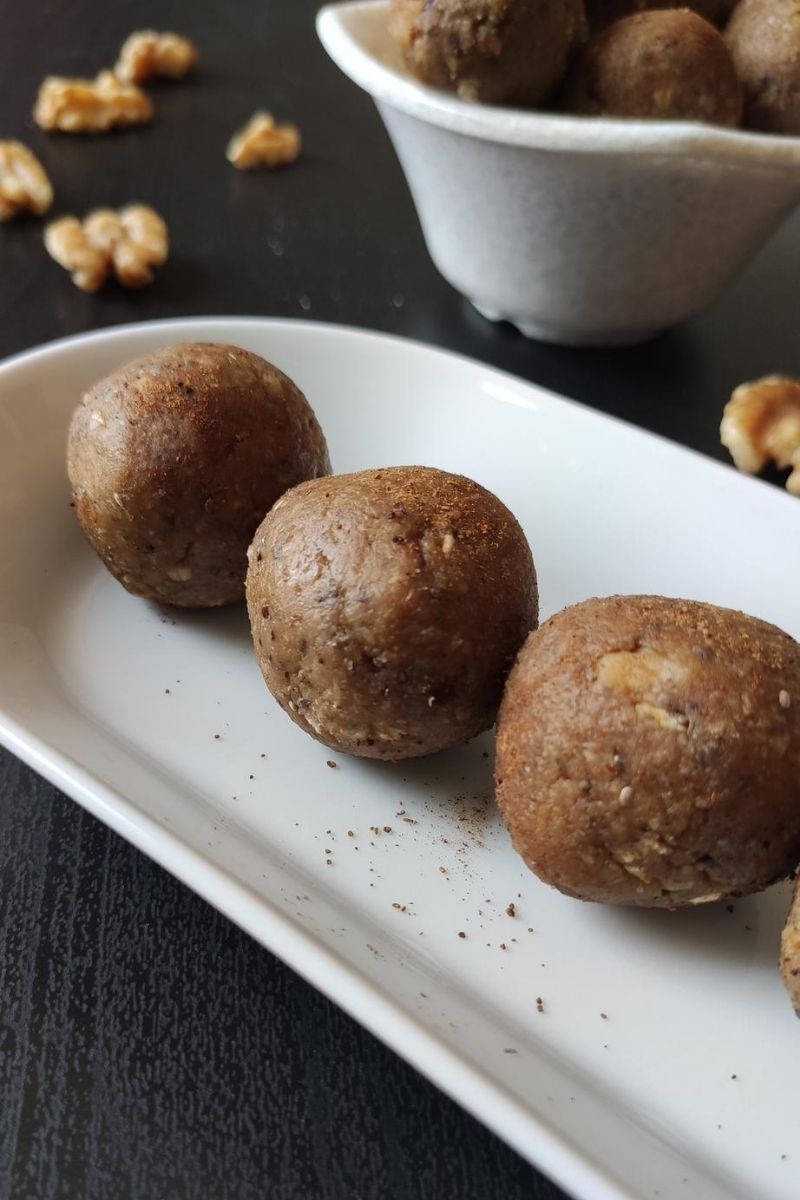 vegan energy balls served on a white snack plate and more kept in a bowl in the background