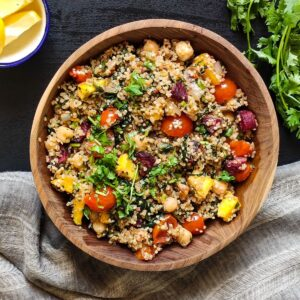 healthy quinoa dish in a wooden bowl with lemon wedges and coriander leaves in the background
