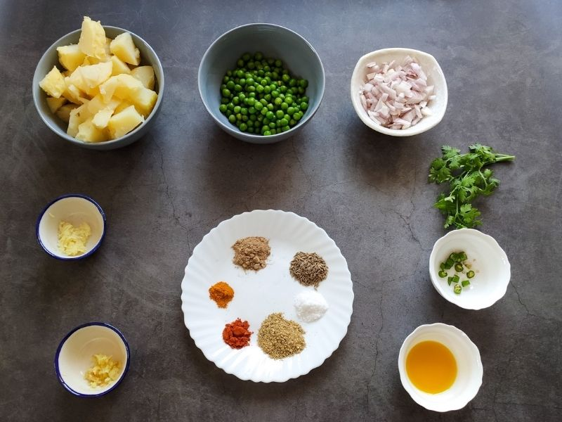Ingredients for dry aloo matar recipe on a grey surface