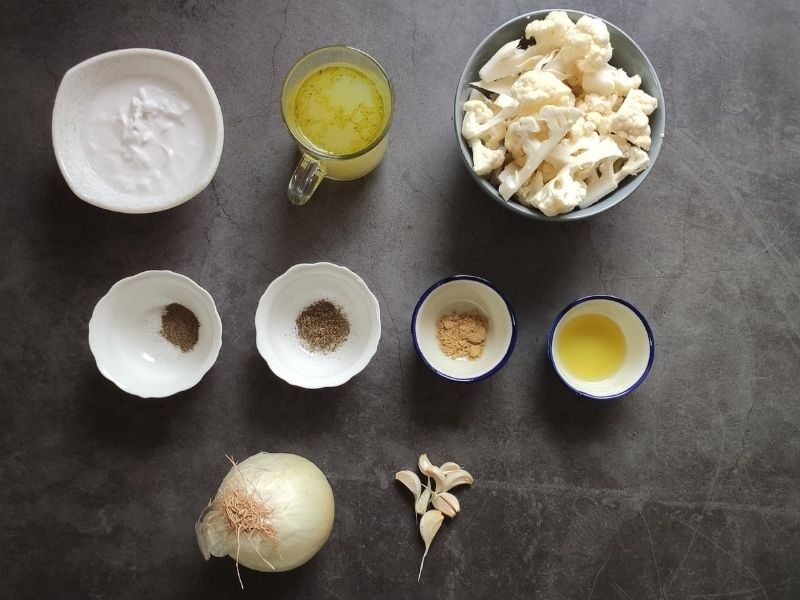 Ingredients for roasted cauliflower soup on a grey surface