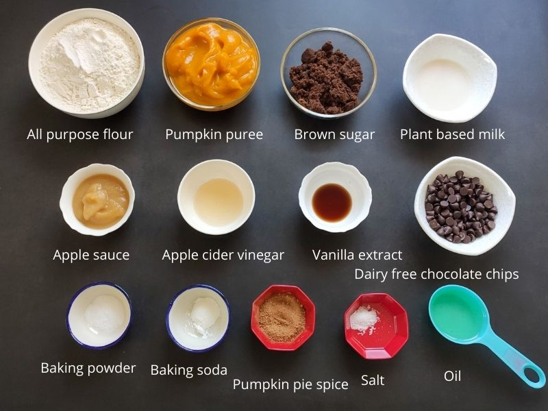 Ingredients of chocolate pumpkin muffins kept on a black surface