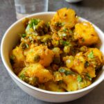 Dry aloo matar served in a white bowl with a glass of water in the background