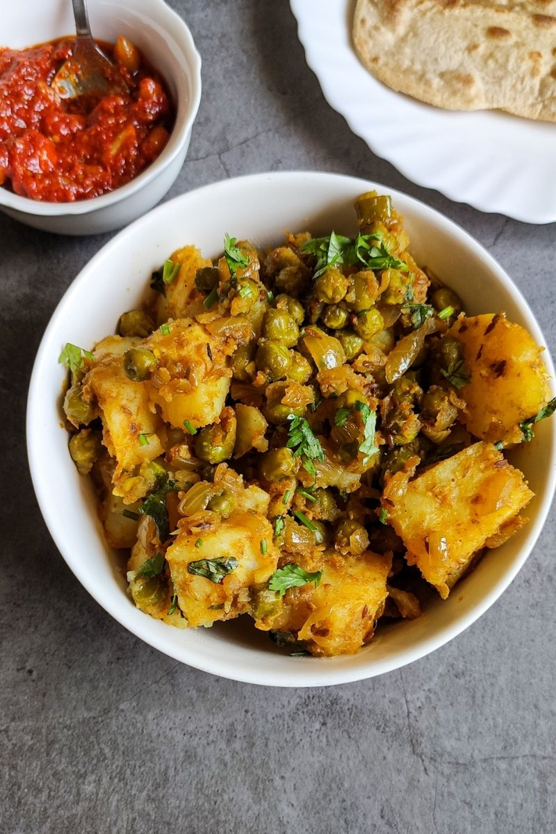 Aloo matar served in a white bowl with pickle and paratha in the background