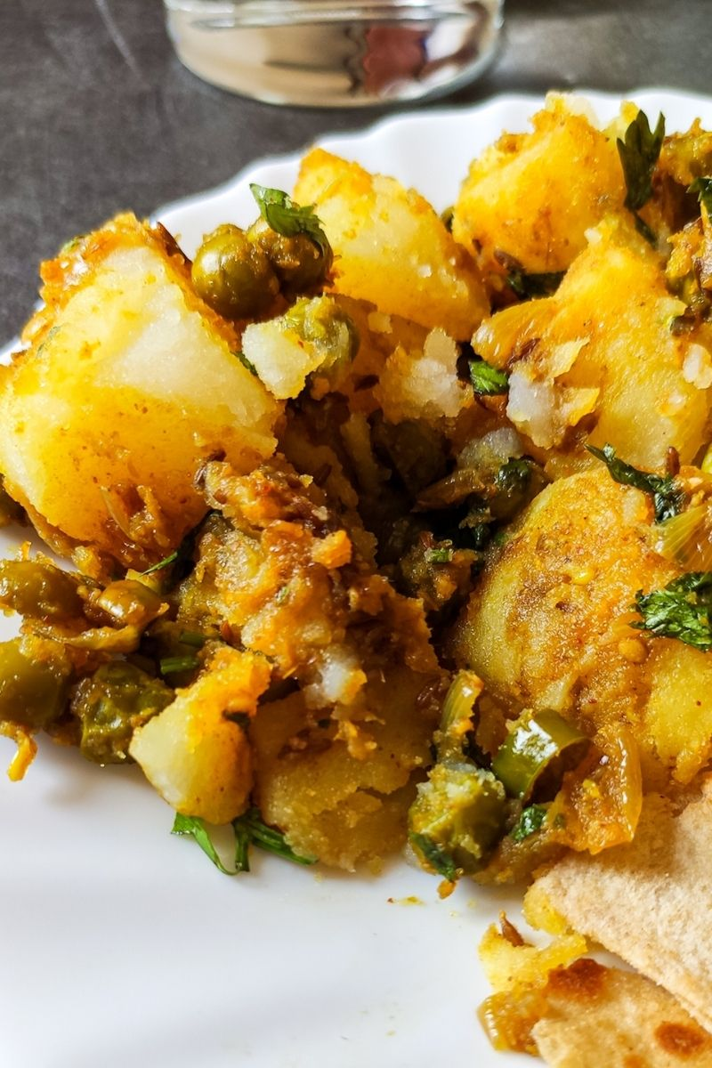 Dry aloo matar with paratha served on a white plate