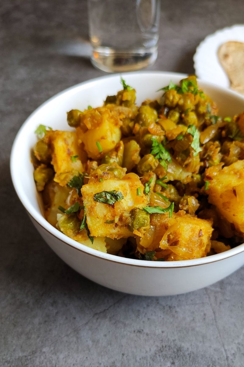 Aloo matar served in a white bowl with a glass of water and paratha in the background