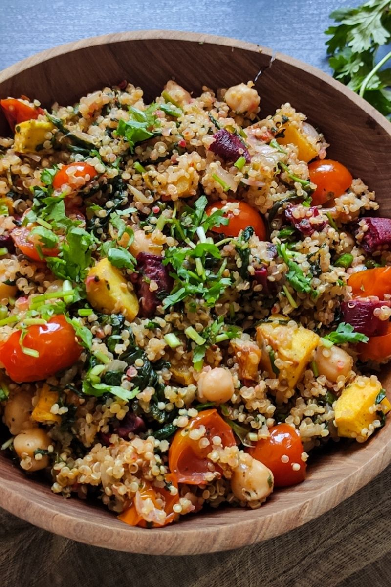 quinoa with cherry tomatoes and vegetables served in a wooden bowl