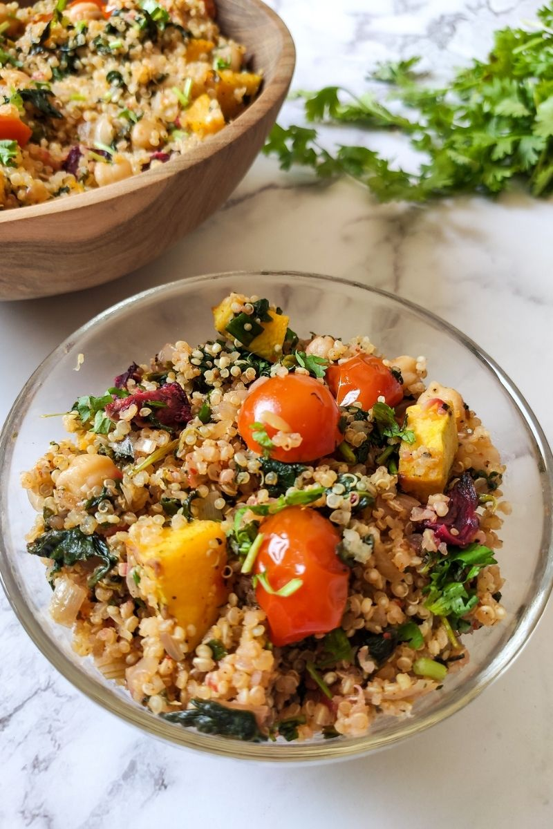 quinoa with vegetables served in a glass bowl another bowl of quinoa and coriander leaves in the background