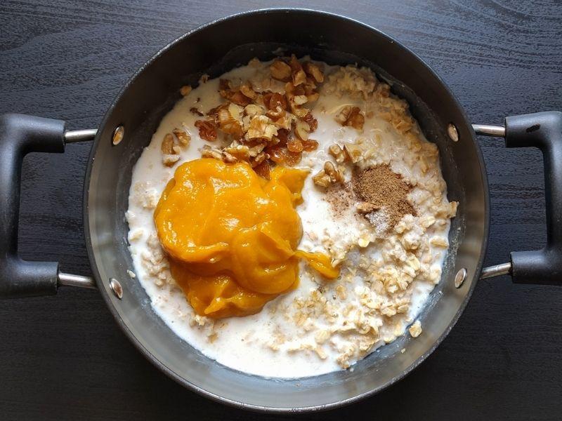 Ingredients of pumpkin oatmeal in a black pot