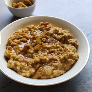 Pumpkin oatmeal served in a white bowl with some walnut kernels in the background
