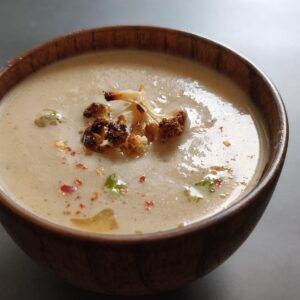 roasted cauliflower soup served in a wooden bowl