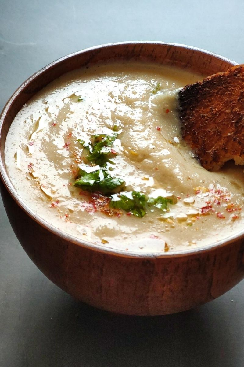 toasted bread dipped in a bowl of cauliflower soup