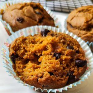 Half eaten pumpkin chocolate muffin more muffins in the background