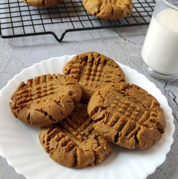 Peanut butter cookies on a white plate with a glass of milk and more cookies in the background